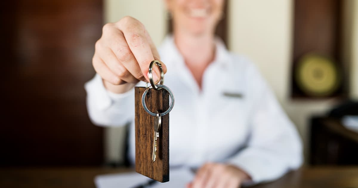 hotel concierge handing a roomkey to the camera