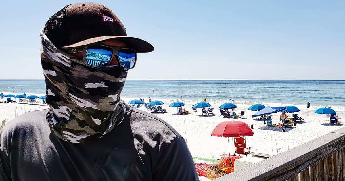Man wearing a bandana face cloth at the beach in california during Covid-19