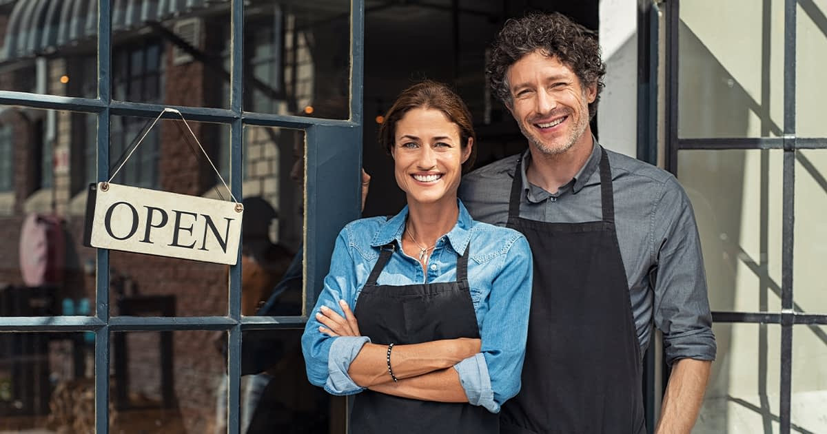 Small business owners in front of a store and open sign