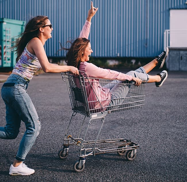 a woman pushing a shopping cart with her friend inside it