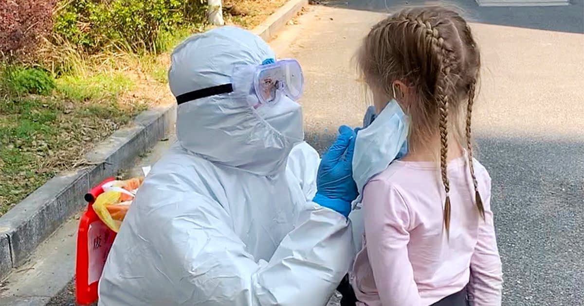 haz mat doctor examining a masked child outside