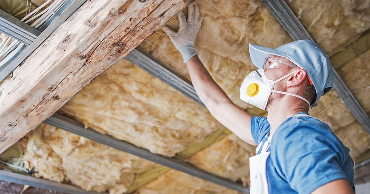 "img src=""Handyman installing insulation on a roof.""/>"
