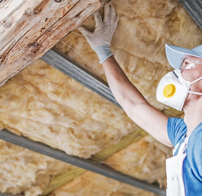 "img src=""Handyman installing insulation on a roof.""/>"